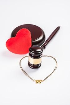Conceito de lei do casamento hindu mostrando martelo de madeira, mangalsutra e brinquedo com coração de pelúcia vermelho, foco seletivo