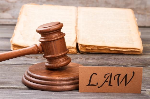 Conceito de lei e justiça. martelo de madeira com livro antigo e palavra de lei.