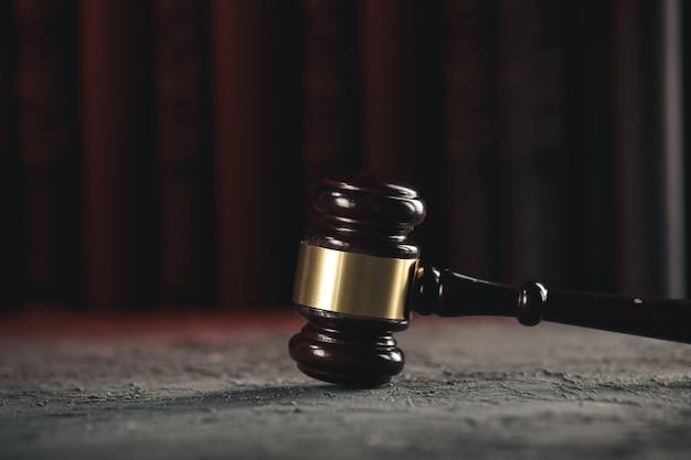 Conceito de lei - livro de direito aberto com um martelo de madeira dos juízes na mesa de um tribunal ou escritório de aplicação da lei sobre fundo preto.