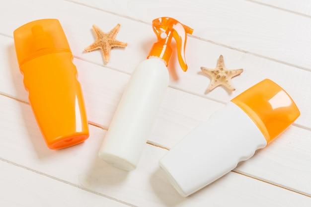 Conceito de leigos plana viagens de férias de verão. garrafas de protetor solar com estrela do mar na mesa de madeira branca com espaço de cópia