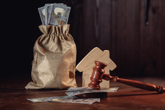 Conceito de leilão de imóveis, saco de dinheiro com caixa e martelo do juiz.