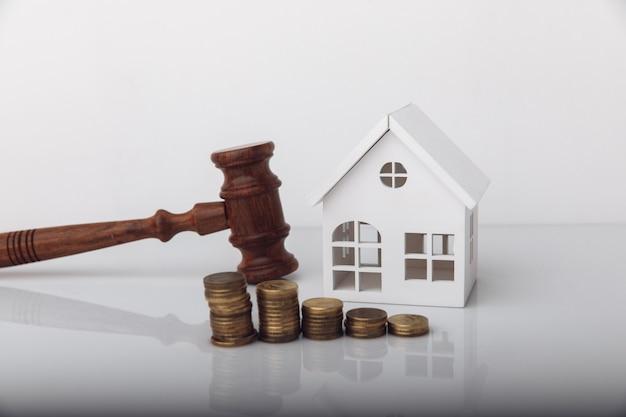 Conceito de leilão de venda de imóveis martelo de madeira e modelo de casa com moedas