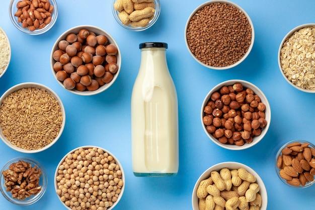 Conceito de leite vegetal com garrafa de leite e tigelas com vista superior de grãos