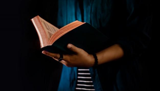 Conceito de leitura. pessoa que mantém aberto o livro da bíblia na mão. imagem escura, recortada
