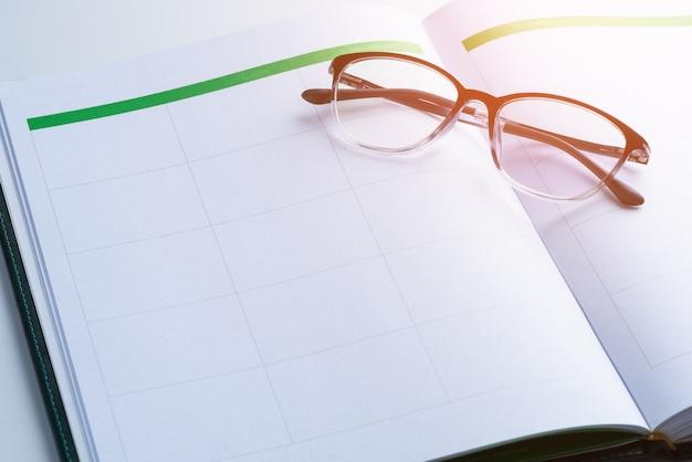 Conceito de lembrete de negócios com livro de nomeação, óculos