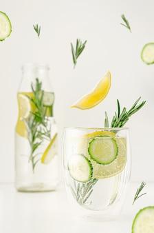 Conceito de levitação de alimentos. desintoxicação de água ou limonada com limão, pepino e alecrim em um copo. perda de peso e estilo de vida saudável.