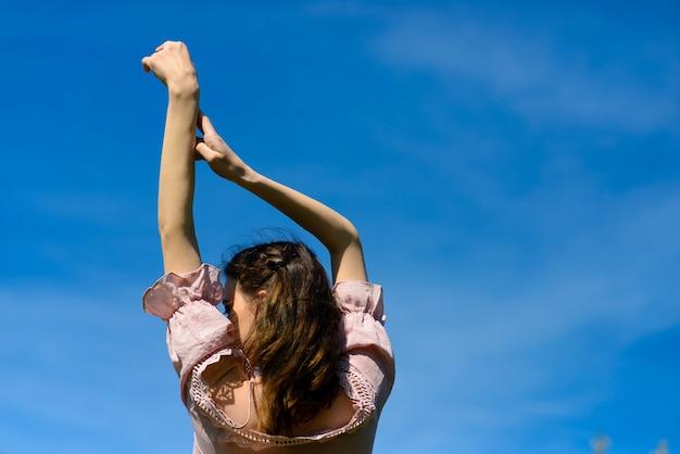 Conceito de liberdade de felicidade felicidade. mulher feliz sorrindo alegre com os braços levantados dançando no verão