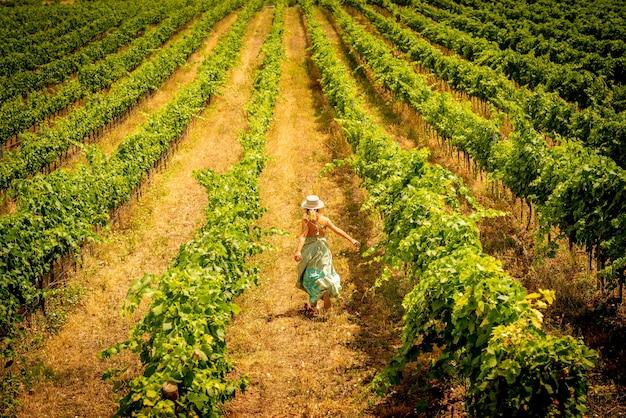Conceito de liberdade e felicidade de pessoas curtindo a natureza - mulher vista de costas correndo livre na natureza do vinhedo ao ar livre - conceito de viagens e estilo de vida alegre - senhora de estilo de moda moderno desfrutar do país