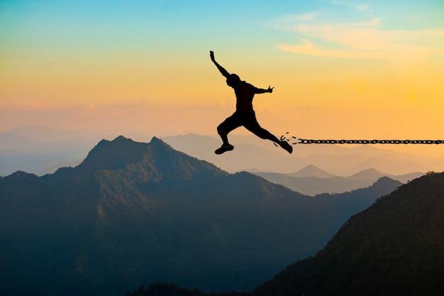 Conceito de liberdade, silhueta de um homem pulando e correntes quebradas na montanha com o céu do sol.