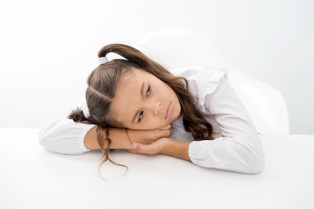 Conceito de lição de casa. menina não quer fazer lição de casa. menina triste e cansada isolada no branco. de volta à escola.