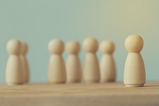 Conceito de líder de equipe de negócios bem sucedido: figuras de madeira de homem e pessoas que se destacam da multidão. descreve a gestão de recursos humanos e o recrutamento de funcionários ou contratados.