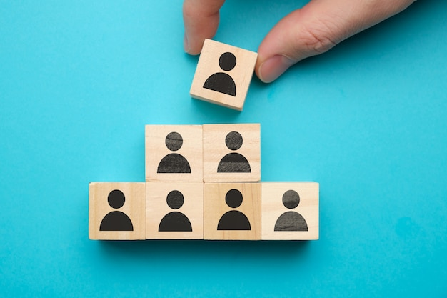 Conceito de liderança - blocos de madeira com pessoas abstratas em um espaço azul.