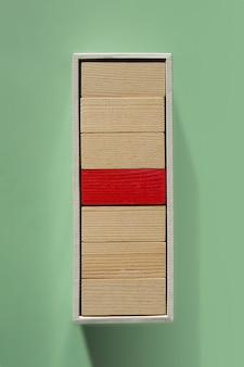 Conceito de liderança e influenciador. um vermelho e muitos blocos de madeira empilhados na caixa. individualidade e singularidade. líder ou chefe dominante.