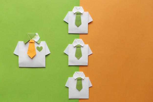 Conceito de liderança e trabalho em equipe, camisa amarela de origami com gravata e líder entre a pequena camisa amarela