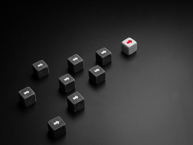 Conceito de liderança, gerente, ceo, influenciador, formador de opinião e líder de negócios. o líder com uma seta vermelha em dados brancos liderando o grupo de dados pretos com seta branca, seguidores em fundo escuro.