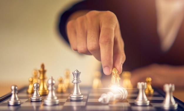Conceito de liderança, homem de negócios fazendo a figura de xadrez em movimento no sucesso da competição.