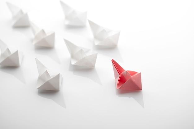 Conceito de liderança usando navio de papel entre brancos