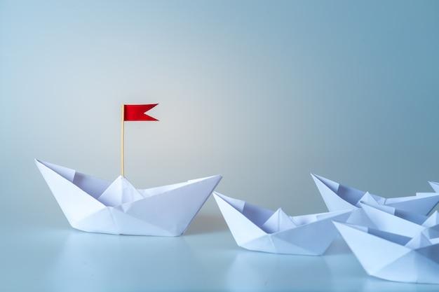 Conceito de liderança, usando o navio de papel com bandeira vermelha em fundo azul