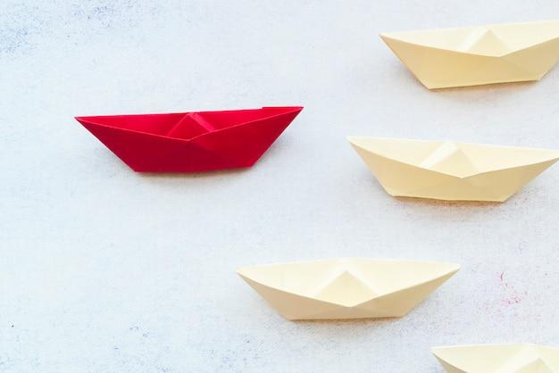 Conceito de liderança, usando o navio de papel vermelho entre branco no pano de fundo
