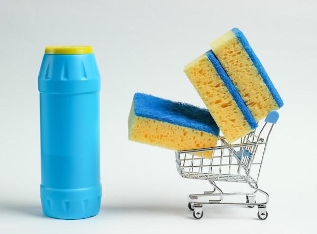 Conceito de limpeza. carrinho de compras com frasco de detergente, esponjas no fundo branco