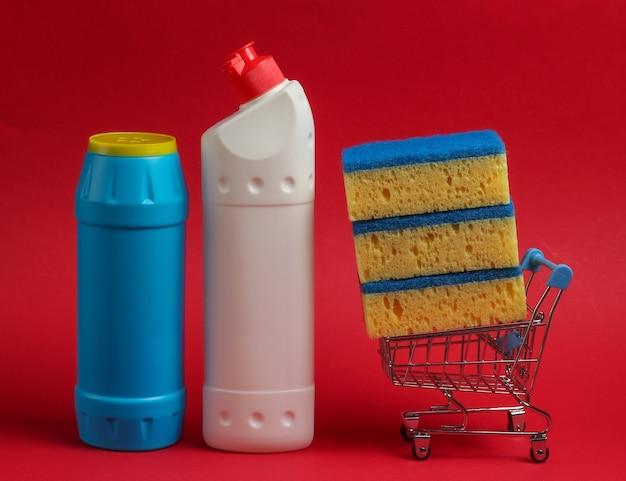 Conceito de limpeza. carrinho de compras com frascos de detergentes, esponjas em um fundo vermelho