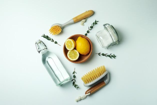 Conceito de limpeza com ferramentas de limpeza ecológicas e limões em fundo branco isolado