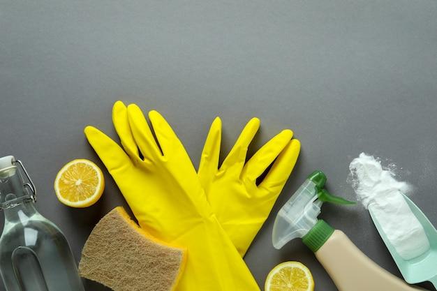Conceito de limpeza com ferramentas de limpeza ecológicas e limões em fundo cinza isolado