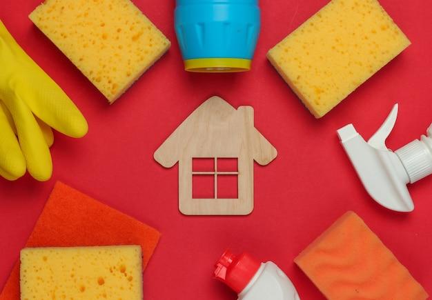 Conceito de limpeza. conjunto de produtos para limpeza e figura da casa sobre fundo vermelho. vista do topo.