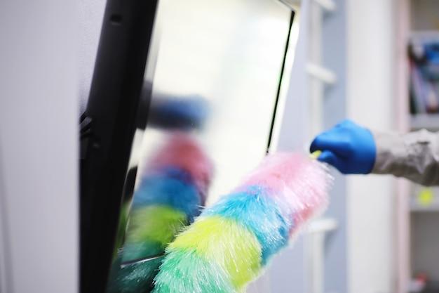 Conceito de limpeza de casa. limpe a poeira das superfícies. tratamento desinfetante de maçanetas de portas de tv elétrica. tratamento sanitário domiciliar em quarentena.