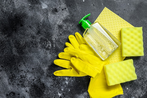 Conceito de limpeza de cozinha amarela, limpeza, higiene, primavera, tarefas, material de limpeza. fundo preto. vista do topo. copie o espaço.