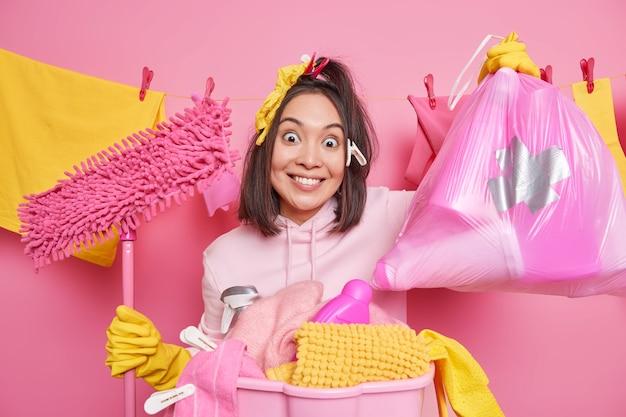 Conceito de limpeza de primavera. a dona de casa asiática positiva segura um saco de detergentes de limpeza, lava a roupa em casa, limpa as poses do quarto contra as roupas penduradas no varal com prendedores de roupa conceito de limpeza