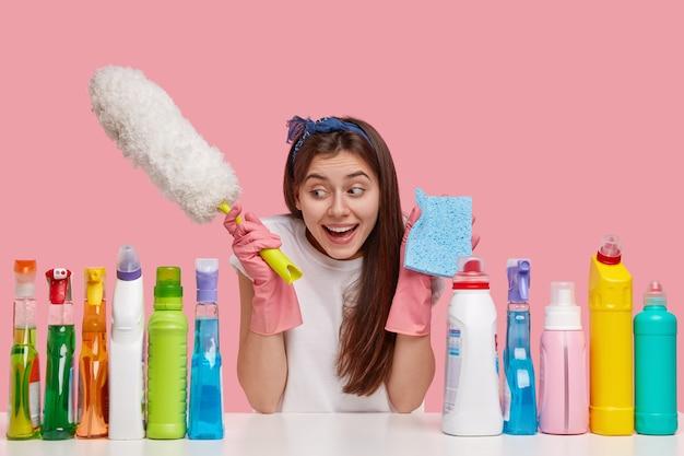 Conceito de limpeza de primavera. morena satisfeita, jovem caucasiana, segurando uma escova de pó e uma esponja azul, sorrindo positivamente