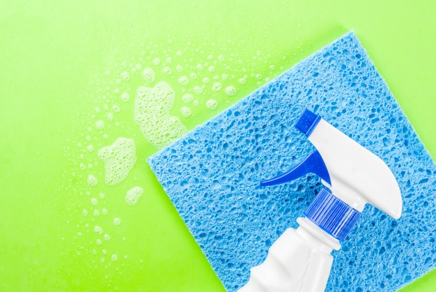 Conceito de limpeza de primavera spray de limpeza, esponjas com espuma no espaço da cópia de superfície verde