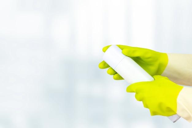 Conceito de limpeza de primavera. vista superior da mão em luvas de borracha amarelas segurando o ambientador pulverizado. conceito de limpeza, serviço de limpeza.