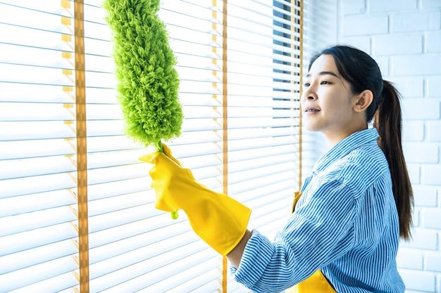 Conceito de limpeza e limpeza, jovem feliz em luvas de borracha amarela, limpando o pó usando a vassoura de penas durante a limpeza na janela em casa