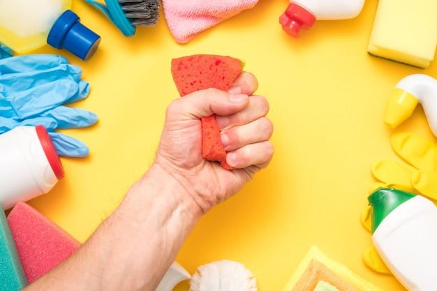 Conceito de limpeza em casa. esponja de aperto de mão de homem. quadro de suprimentos variados em amarelo.