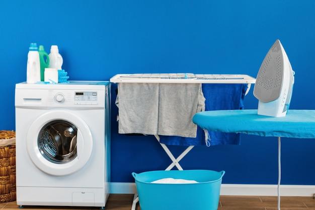 Conceito de limpeza. máquina de lavar roupa e tábua de passar roupa