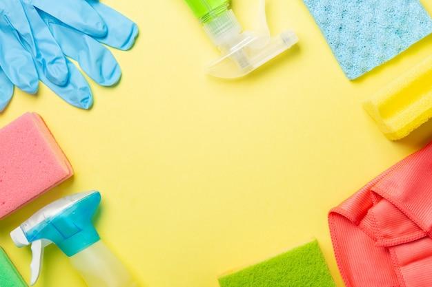 Conceito de limpeza - material de limpeza, luvas, garrafas em fundo amarelo pastel, copie o espaço