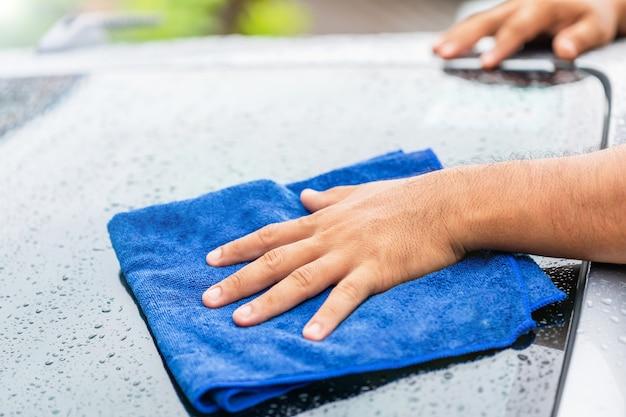 Conceito de limpeza ou lavagem do carro: mão segurando um pano azul para limpar o corpo molhado do carro moderno tiro ao ar livre em dia de chuva.