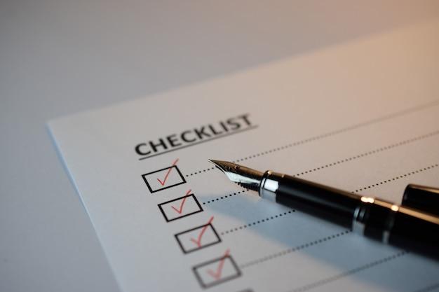 Conceito de lista de verificação - caixa de lista de verificação com marca de seleção vermelha, papel e uma caneta com a palavra lista de verificação na tabela