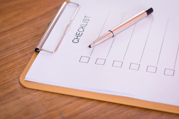 Conceito de lista de verificação - lista de verificação, papel e uma caneta com a palavra de lista de verificação na mesa de madeira