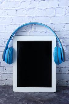Conceito de livro de áudio. fones de ouvido e tablet digital na mesa.