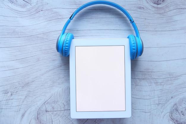 Conceito de livro de áudio. fones de ouvido e tablet digital na mesa