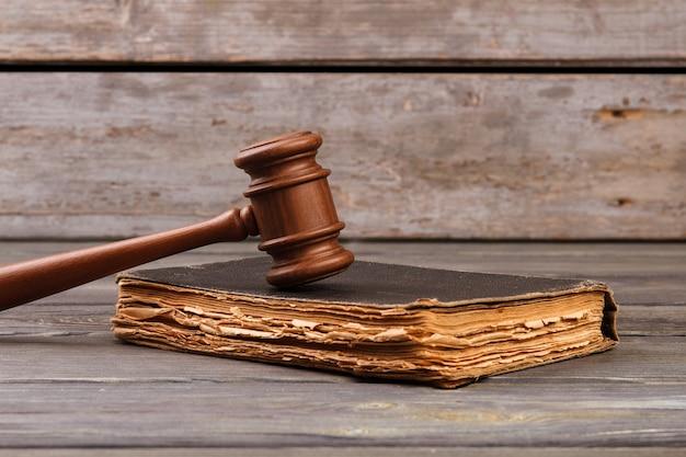 Conceito de livro jurídico. martelo de madeira no livro velho e gasto.