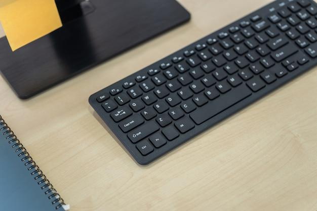Conceito de local de trabalho, tecnologia e negócios. close-up do teclado preto do computador na mesa de madeira com monitor, papel e caderno.