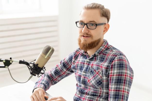 Conceito de locutor de rádio - homem bonito trabalhando como locutor de rádio em uma estação de rádio