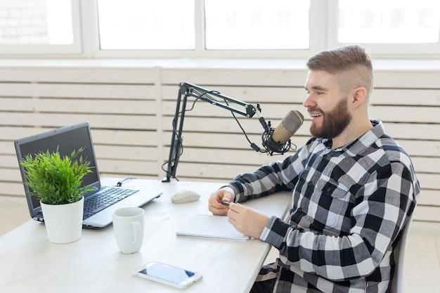 Conceito de locutor de rádio - vista lateral de um homem bonito trabalhando como locutor de rádio em uma estação de rádio