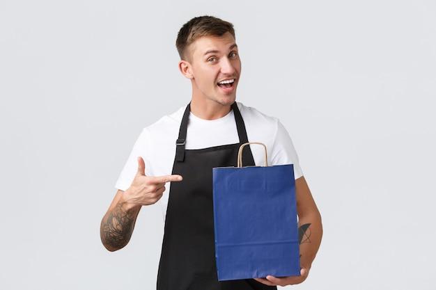 Conceito de loja, compras e funcionários de varejo. vendedor amigável e entusiasmado de avental preto, apontando o dedo para a eco-bag com produtos comprados por clientes, fundo branco em pé
