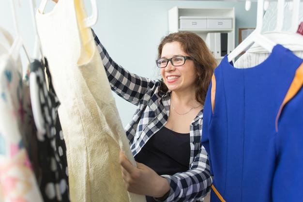 Conceito de loja de moda e pessoas - mulher escolhendo roupas na frente do armário cheio
