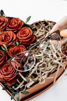 Conceito de loja de óculos óculos no fundo de rosas vermelhas óculos na mão do oftalmologista